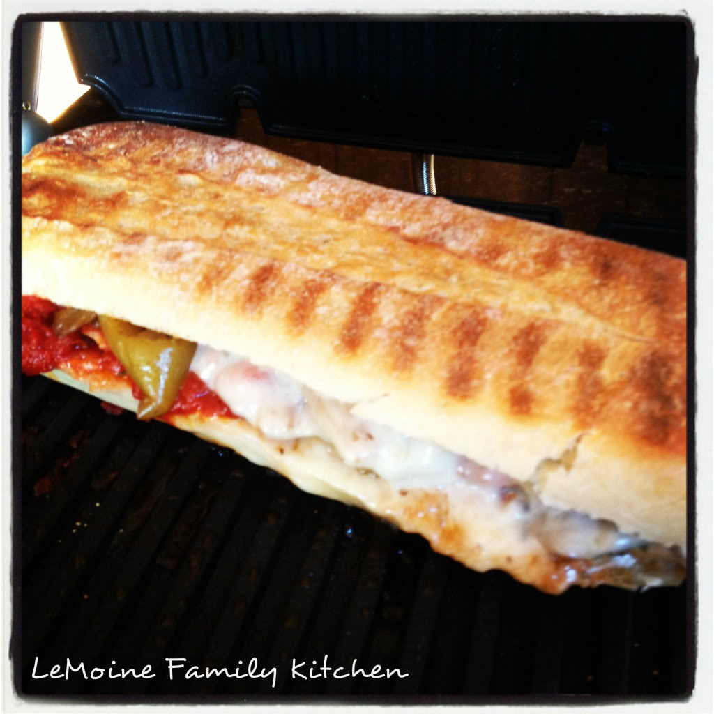 Italian Pork Panini. Perfectly roasted pork sliced thin, topped with peppers, onions, tomato sauce and cheese then pressed with a good hearty bread.