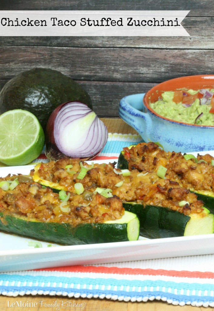 Chicken Taco Stuffed Zucchini  | LeMoine Family Kitchen. Lean ground chicken cooked up with peppers, onions, taco seasoning and salsa verde. All stuffed into zucchini and baked. Topped with cheddar and scallions. This is a DELICIOUS and healthy meal!