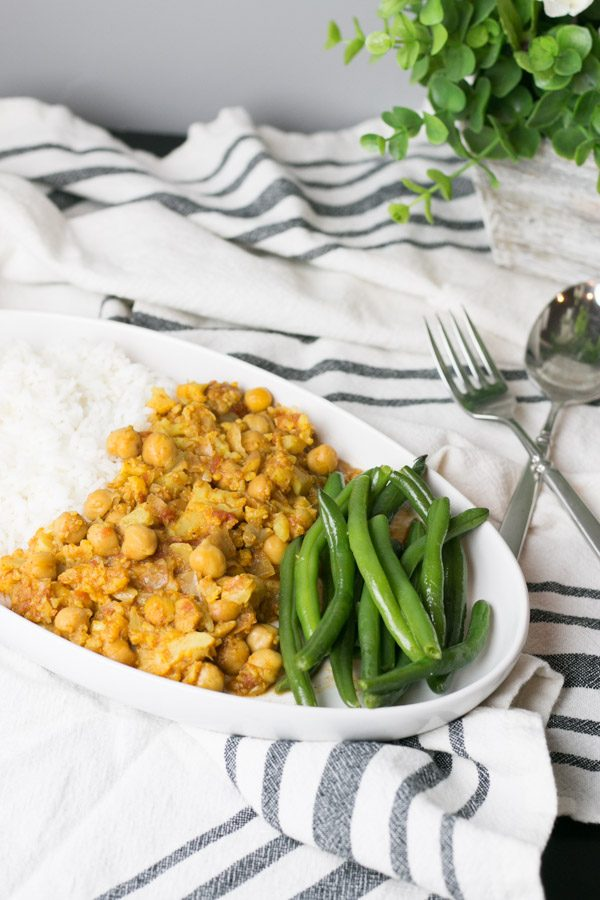 Anyone else working towards a goal of a healthier 2018? I know we certainly are, especially after eating all those Christmas cookies! Today I'm sharing with you a really simple meal that is not only easy to throw together for a weeknight meal but is super flavorful and vegetarian friendly too! This Chickpea Cauliflower Curry is spicy, filling and so tasty!