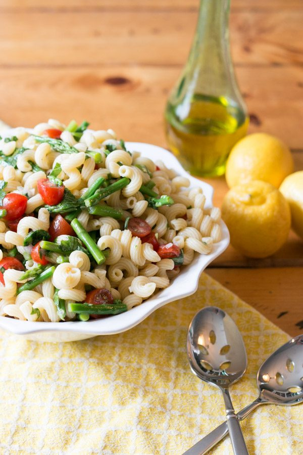 The weather is finally warming up and I am super excited for outdoor entertaining! This Lemon Basil Pasta Salad with Asparagus & Tomato is bursting with flavor and the perfect addition to any summer get together!